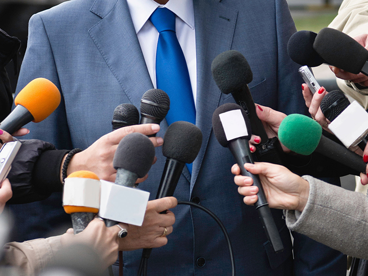 Reporters hold microphones up to a man in a suit