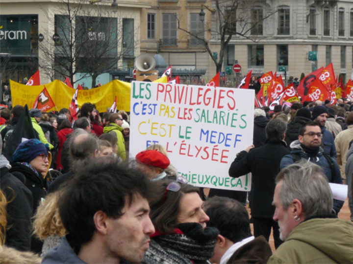 A crowd protests with flags and a sign (in French)