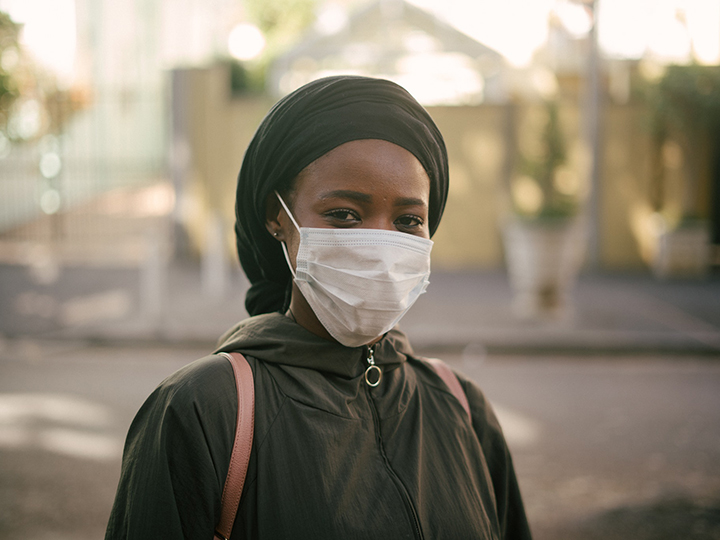 Woman in a headscarf wearing a disposable mask