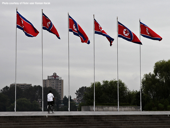 Six tall North Korean flag poles next to each other as man rides his bicycle below them (via Flickr user Roman Harak)