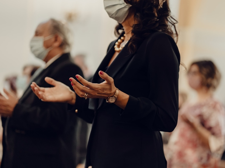 Woman in church wearing a face mask and praying with her hands outstretched