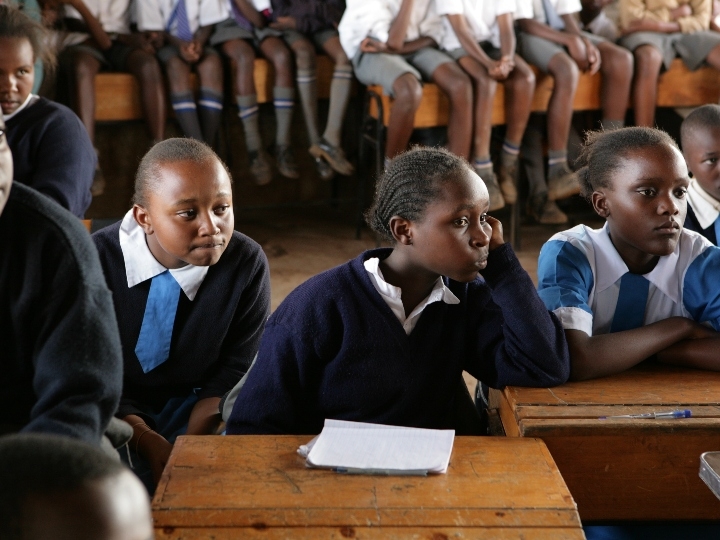 Young girls in school uniforms listening during class