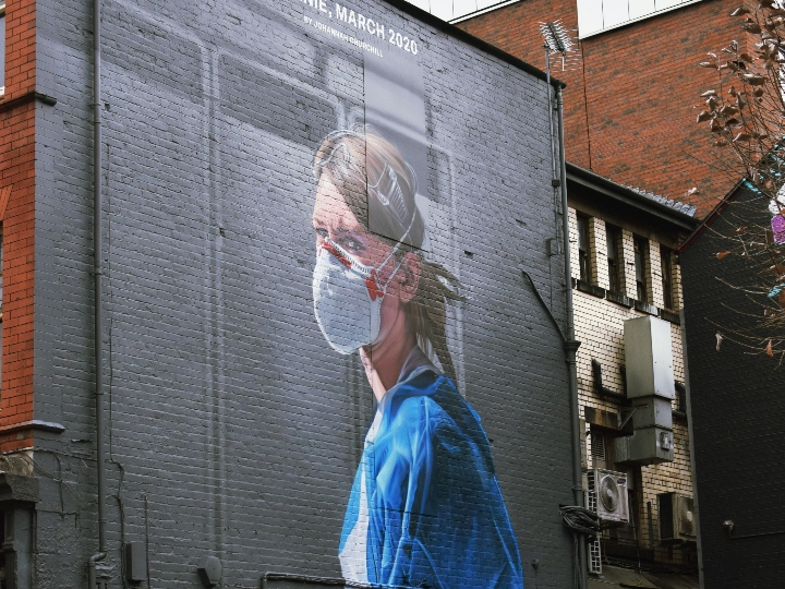 Mural of female healthcare worker in PPE on city building