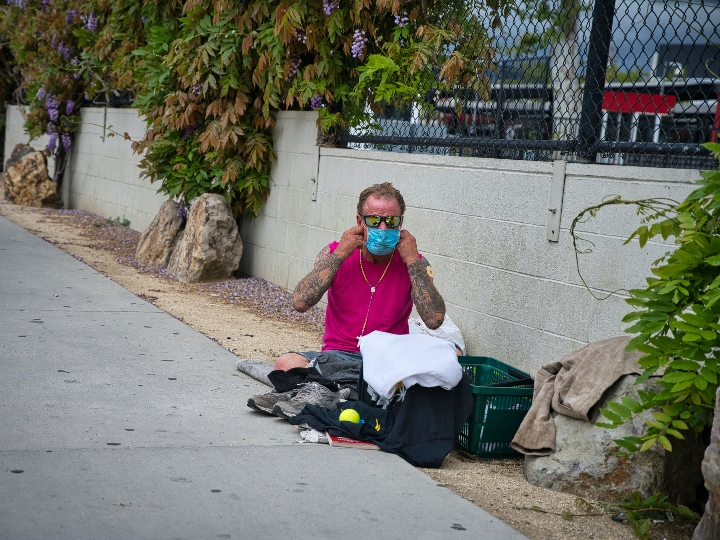 A homeless man on the sidewalk puts on his face mask during the COIVD outbreak
