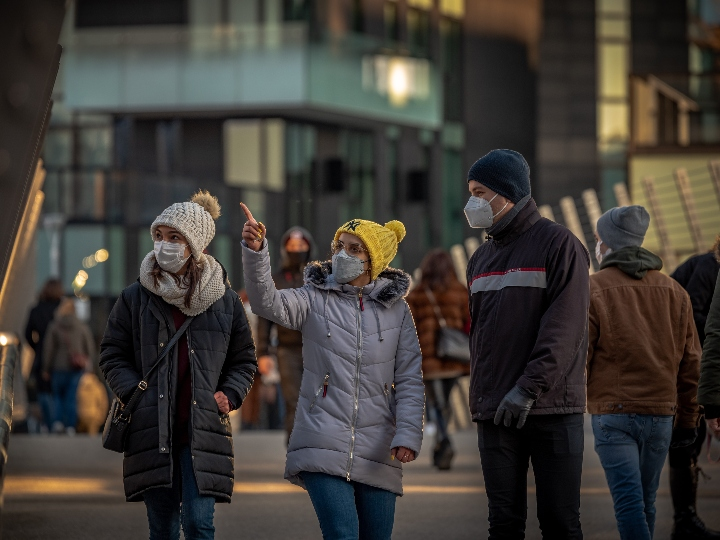Two women and a man wearing masks and walking in public