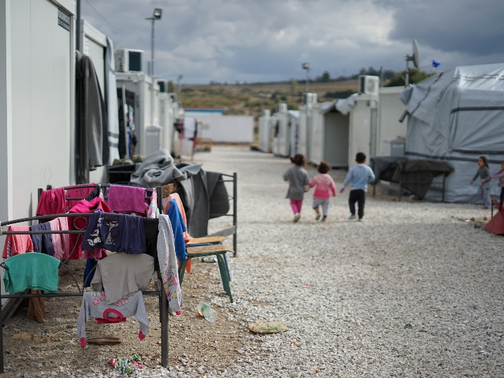 Three children walking in a Syrian refugee camp