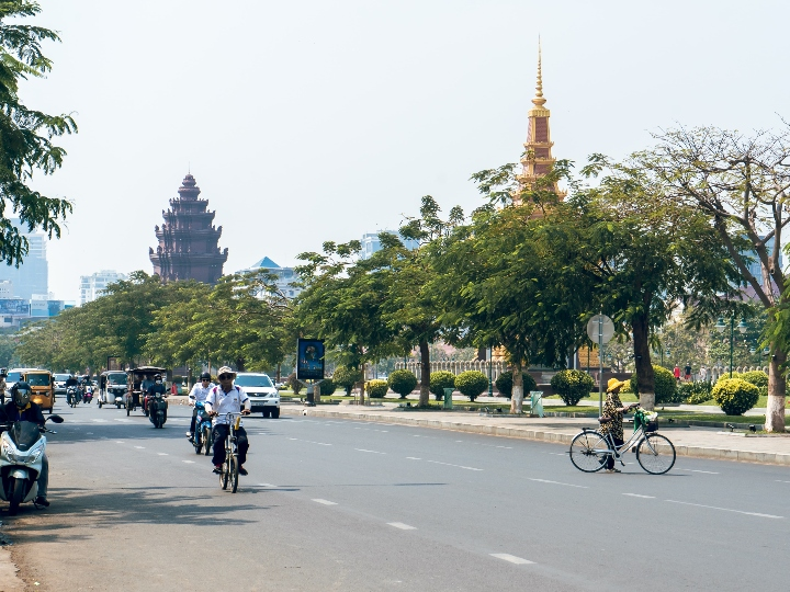 Street view of Phnom Penh, Cambodia with notable Cambodian architecture in the background