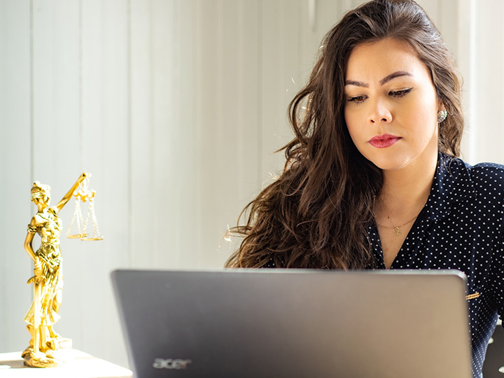 Young professional woman typing on a computer next to a small gold statue of Lady Justice