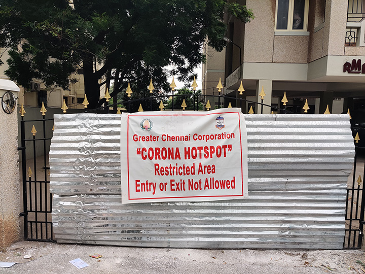 "Building gate with ""Greater Chennai Corporation Corona Hotspot - Restricted Area Entry or Exit Not Allowed"" sign"