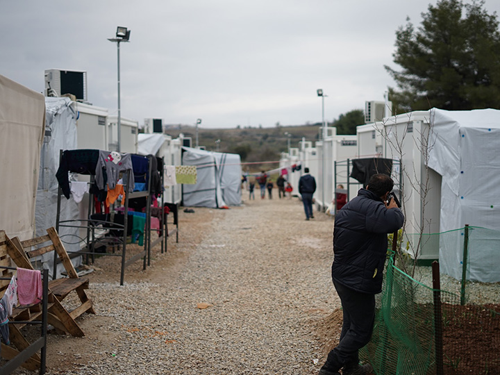 Man talking on a cell phone amid white tents at a refugee camp for Syrian migrants in Greece