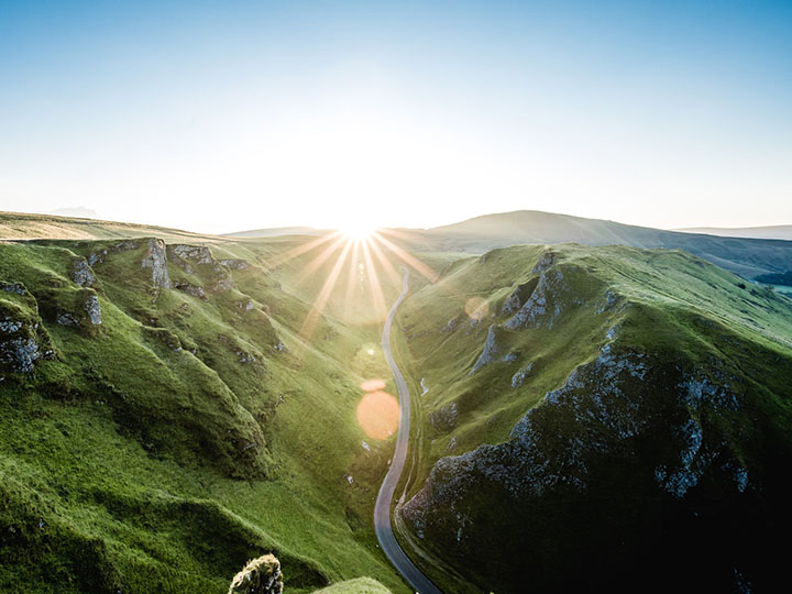 Road between two grassy cliffs ends in a sunrise