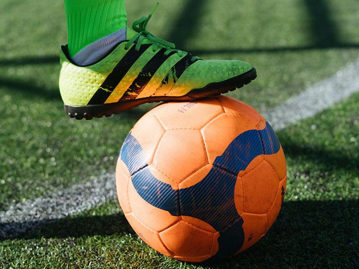 Neon green shoe standing on orange soccer (football) ball