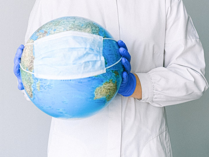 A person wearing a lab coat and gloves holds a mask against a globe