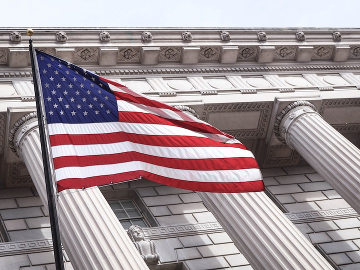 American flag waves outside government building
