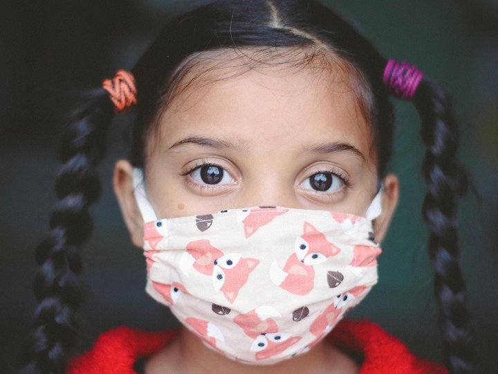 Young girl wearing mask to protect against COVID-19