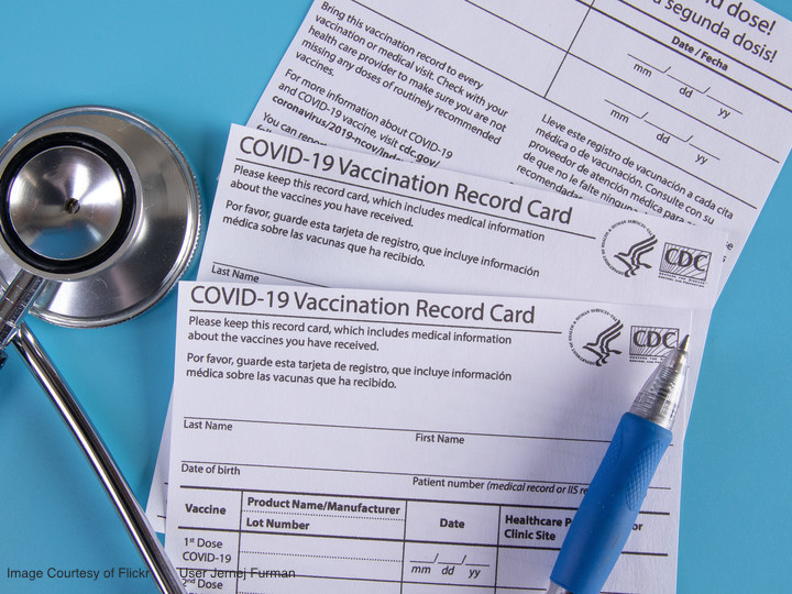 COVID-19 vaccination record cards next to a stethoscope