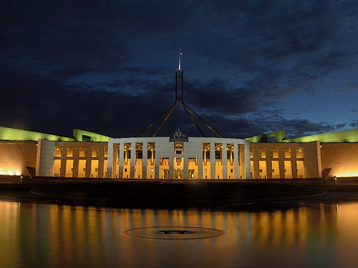 Exterior of the Australian parliament building during the night with lights on inside.