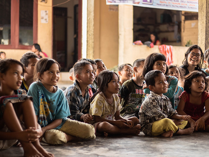 Indonesian elementary school children sit on the floor, looking off to the side and smiling.