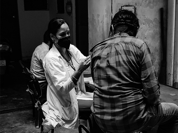 A healthcare professional administers a COVID-19 vaccine in India