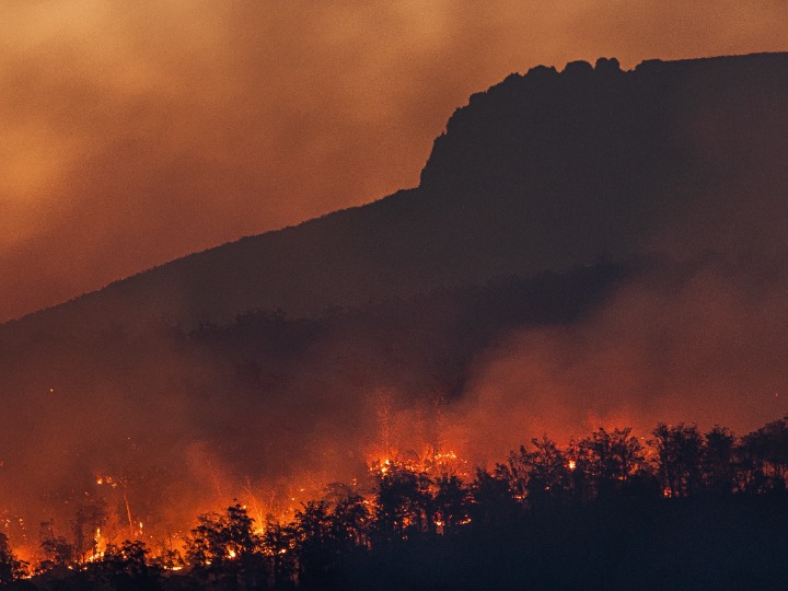Forest fire under a mountain, the sky is orange with smoke.