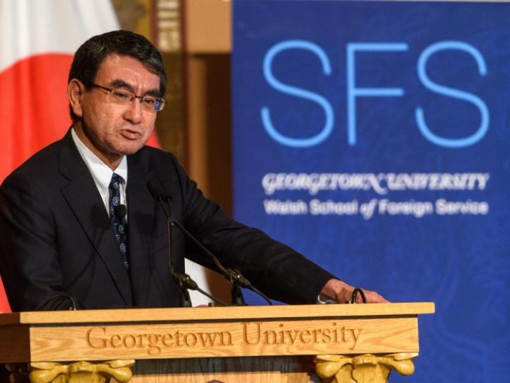Kono Taro giving a speech in Georgetown with an SFS banner behind him.