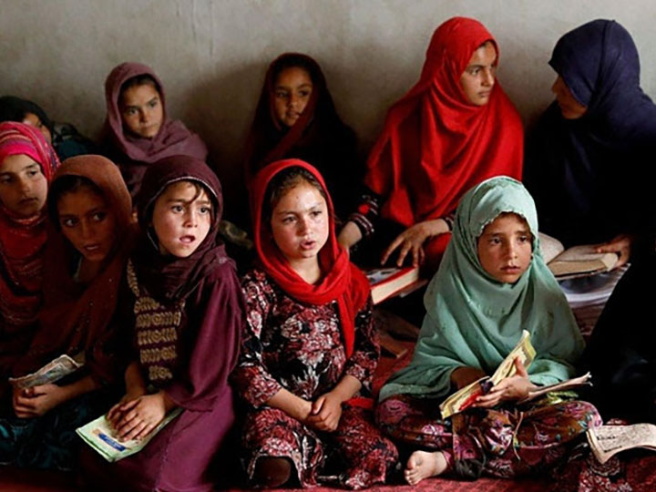 A group of young Afghan girls sitting together with books in their laps.