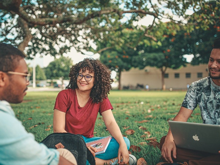 Three students sitting on the lawn on a university campus, laughing and talking.