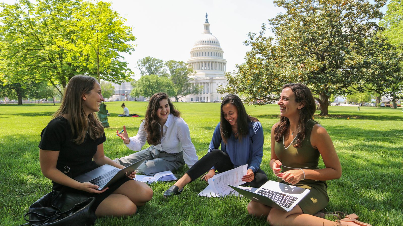 Female Georgetown students sit on the grass with the U.S. Capitol Building in the background