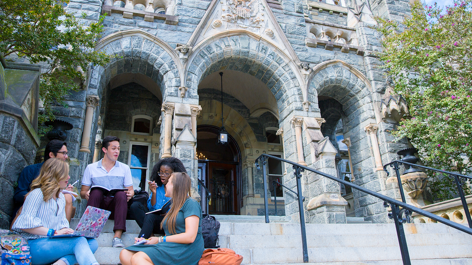 Students studying on the steps of Healy Hall
