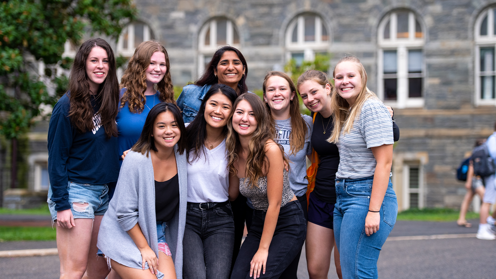 A group of female students smile in front of Healy Hall