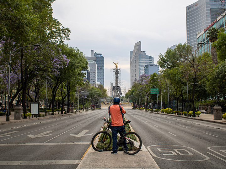 Man on bicycle in empty Paseo de la Refoma in Mexico City
