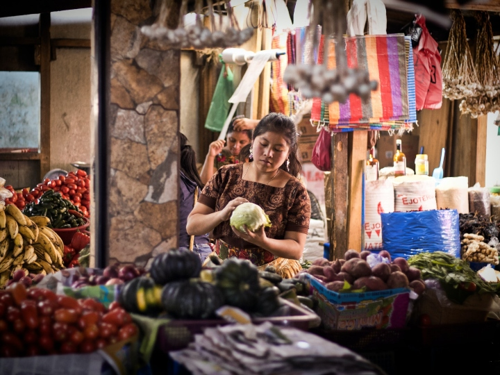 A woman manages a vegetable stand at a market in Guatemala