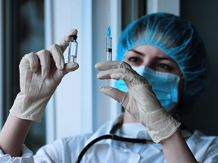 Medical person holding a needle and vial