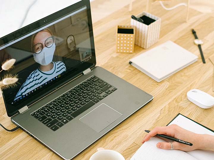 Woman in mask on a video call on a laptop