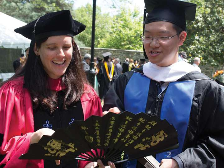 An American woman and Chinese man opening a hand fan with Chinese characters at graduation
