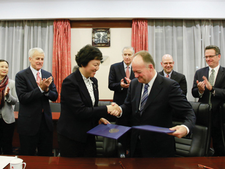 John J. DeGioia and a Chinese woman shaking hands and being applauded at the signing reception