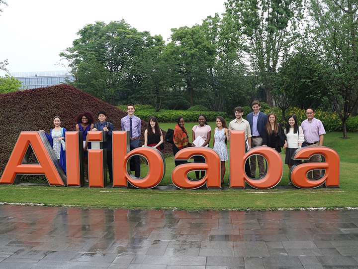 Georgetown students at Alibaba headquarters posing at a Alibaba signage