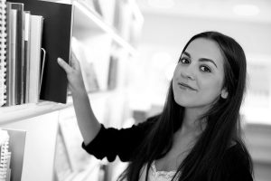 Young brunette woman student trainee or employee smiling while choosing the right book or file from the shelf of an office or a learning library portrait
