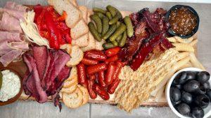 Full board with sausage, pickles, marmalade, and kalamata olives