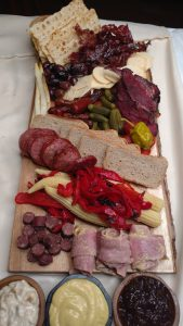 full display of charcuturie board with bread, crackers, meat and mustard