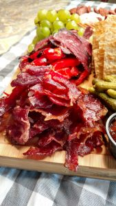 Display of Kosher Charcuterie board, with crispy meat, grapes and crackers