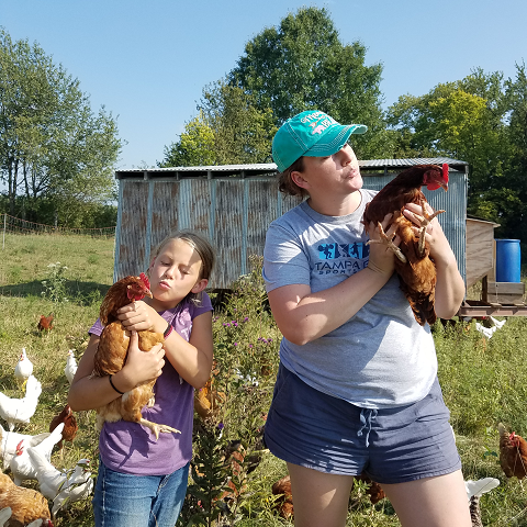 Rivers and Jenna holding laying hens on a sunny day.