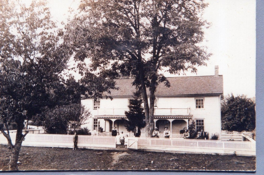 Slusher Homeplace (early 1900s)…Clemmie and George W. are flanking the open gate…Roger is standing to the left of the fellow leaning against the tree.