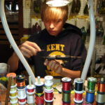 Fly tying class with young tyer surrounded with fly tying materials