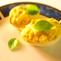 Deviled eggs with shrimp, yellow mustard and basil.