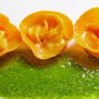 Tortelli di pasta al pomodoro farciti con mozzarella e ricotta di bufala su pesto di basilico