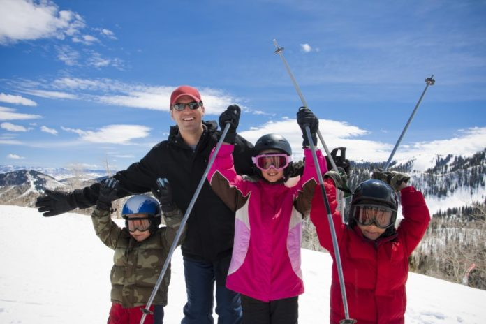 A happy father and his kids on a ski resort vacation in Park City, Utah. Find out what the best family hotels there are