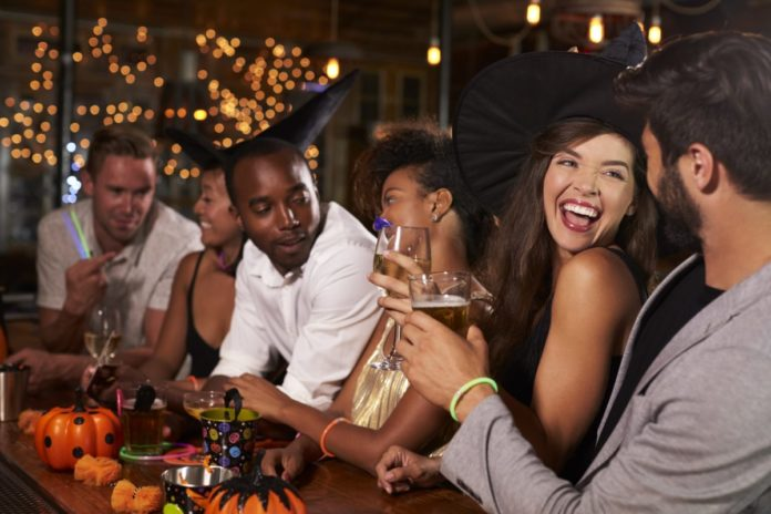 Friends having fun at a Halloween party in a bar. Find out how to save at the best bar crawls in Charlotte, NC