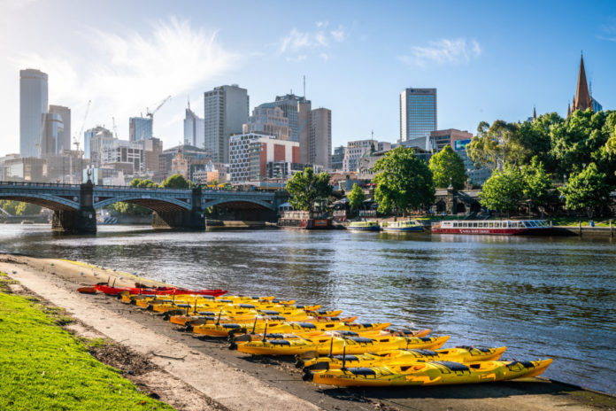 Melbourne buildings skyline with Yarra river view and yellow kayak boats on the riverbank in Melbourne Victoria Australia