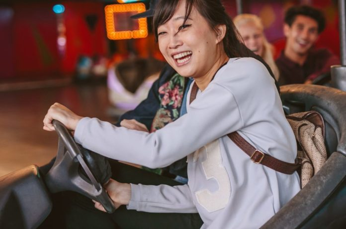 Happy young girl driving a bumper car. Enjoy bumper cars & other rides at Little Amerricka & save money on tickets with a promo code